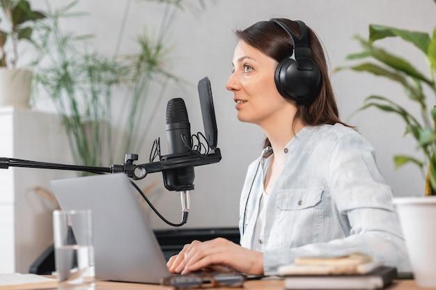 Podcaster tworzy treści europejska kobieta nagrywa podcast z mikrofonem i słuchawkami kaukaskimi