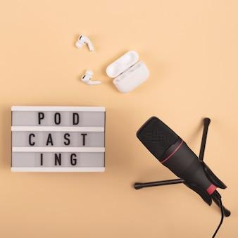 Podcasting napis obok mikrofonu i słuchawek bezprzewodowych w miejscu pracy na beżowym tle