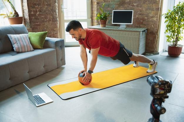 Podciąganie. młody kaukaski mężczyzna trenuje w domu podczas kwarantanny epidemii koronawirusa, robi ćwiczenia fitness, aerobik. nagrywanie wideo lub przesyłanie strumieniowe online. wellness, sport, koncepcja ruchu.