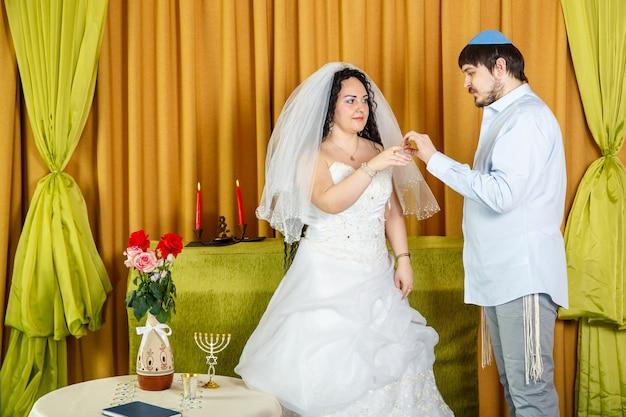 Podczas ceremonii czupy na weselu w żydowskiej synagodze pan młody zakłada pierścień na palec wskazujący panny młodej. poziome zdjęcie