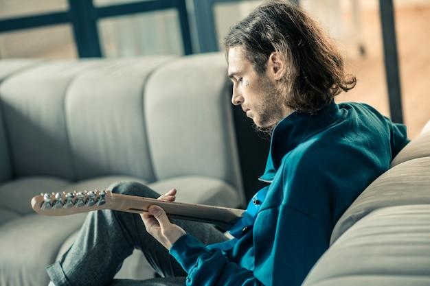 Podczas codziennych powtórzeń. skupiony ciemnowłosy mężczyzna z zarostem spokojnie grający na gitarze będąc sam w domu