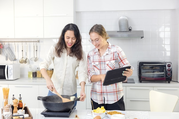 Podczas gotowania posiłków w kuchni szczęśliwa para używa inteligentnego tabletu, aby wyszukać przepis w internecie.