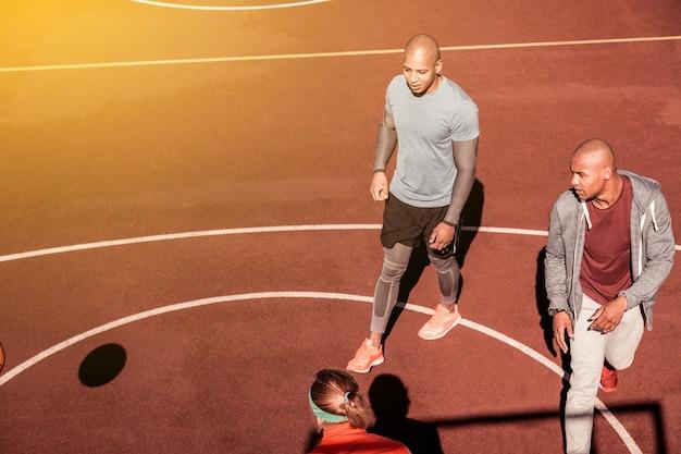 Podczas gry. widok z góry miłych młodych mężczyzn chodzących po boisku do koszykówki podczas gry