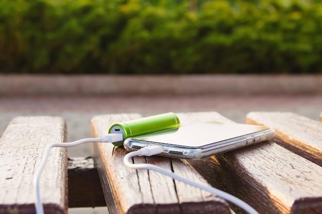 Podczas ładowania smartfon i zewnętrzny bank energii leżą na drewnianej ławce w parku