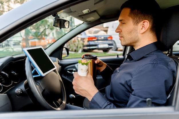 Podczas lunchu kierowca ogląda filmy lub programy telewizyjne na tablecie. zatrzymując się na coś do jedzenia. mężczyzna je przekąskę w samochodzie i pije kawę lub herbatę.