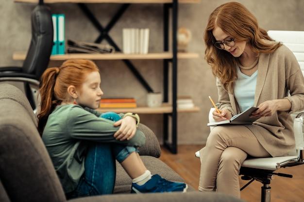 Podczas profesjonalnej konsultacji. miła, sympatyczna psycholog siedzi obok pacjenta i robi notatki w zeszycie