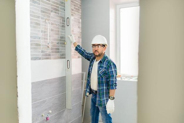 Podczas renowacji budowniczy sprawdza płaskość ułożonych płytek