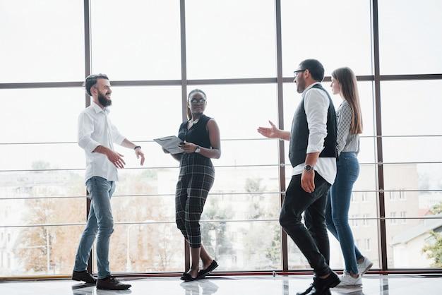 Podczas spotkania w biurze młodzi ludzie biznesu omawiają wspólnie nowe kreatywne pomysły.