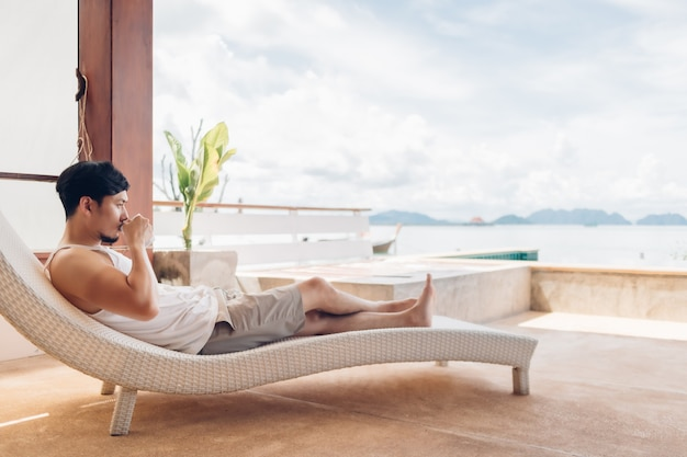 Podczas wakacji mężczyzna leży na ławce, relaksując się z widokiem na morze.