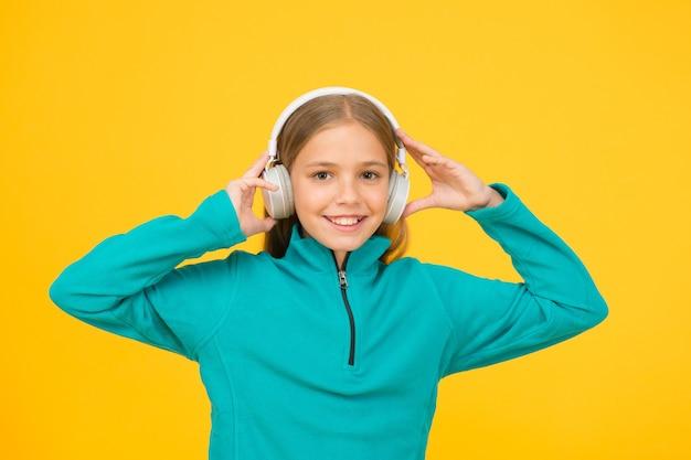 Poddać się krytyce. małe dziecko słuchać muzyki żółte tło. małe dziecko cieszyć się muzyką w słuchawkach. jak muzyka dla moich uszu.