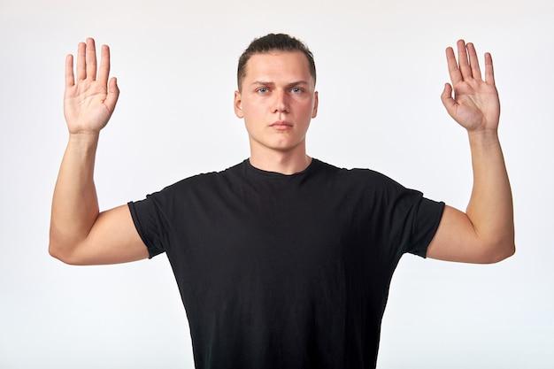 Poddaję się! atrakcyjny młody człowiek podnosi ręce nad białym +