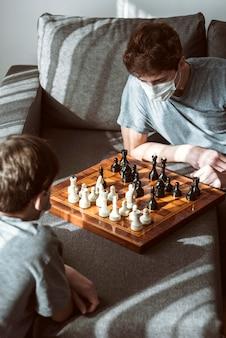 Poddani kwarantannie chłopcy grający w szachy