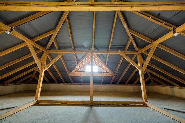 Poddasze budynku z drewnianymi belkami o konstrukcji dachowej i małym oknem.