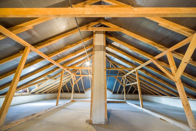 Poddasze budynku z drewnianymi belkami o konstrukcji dachowej.