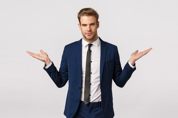 Podejmij decyzję. poważnie wyglądający asertywny i stylowy młody blond biznesmen w klasycznym garniturze, zaproponuj dwa warianty, zdobądź pieniądze, wzbogac się, rozłóż ręce na bok, trzymaj produkt, białe tło