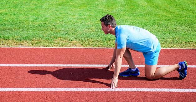 Podejmij wysiłek dla zwycięstwa. biegacz gotowy do drogi. dorosły biegacz przygotowuje wyścig na stadionie. jak zacząć biegać. koncepcja motywacji sportu. człowiek lekkoatleta biegacz stoją niską pozycję startową stadion ścieżka słoneczny dzień.