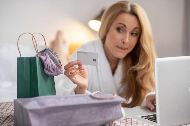 Podejmowanie decyzji. karta kredytowa w ręku całkiem zamyślonej dorosłej kobiety z długimi blond włosami, leżącej przed laptopem na łóżku w sypialni