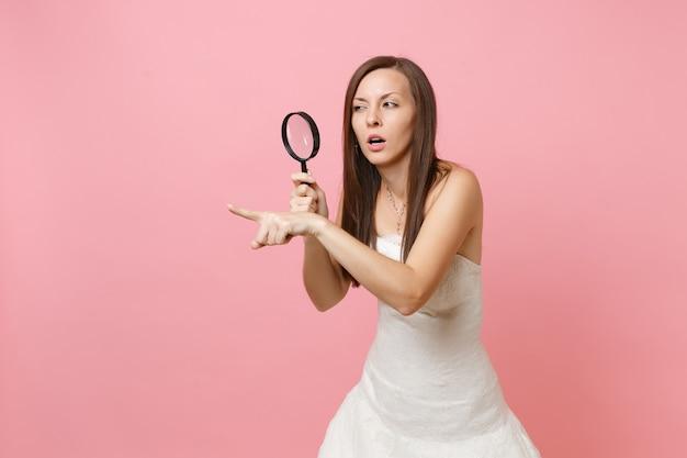Podejrzana kobieta w białej sukni, wskazująca palcem na bok, patrząca przez szkło powiększające