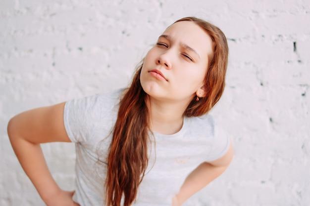Podejrzana nastolatka zmrużyła oczy i patrzy na kamerę na białym murem