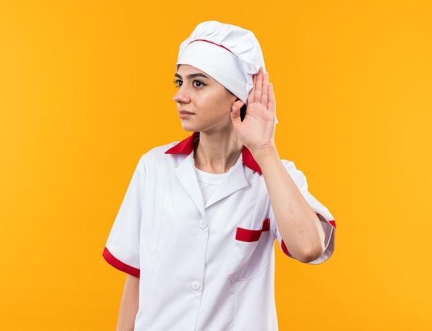 Podejrzana strona młoda piękna dziewczyna w mundurze szefa kuchni pokazująca gest słuchania