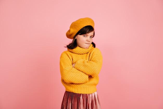 Podejrzany dzieciak w żółtym swetrze. krótkowłosa preteen dziewczyna