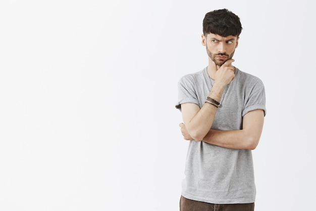 Podejrzany i troskliwy przystojny facet pozuje przy białej ścianie