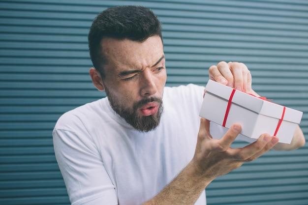 Podejrzany mężczyzna próbuje otworzyć pudełko, aby zobaczyć, co tam jest. nie chce owijać wstążek. na białym tle na paski