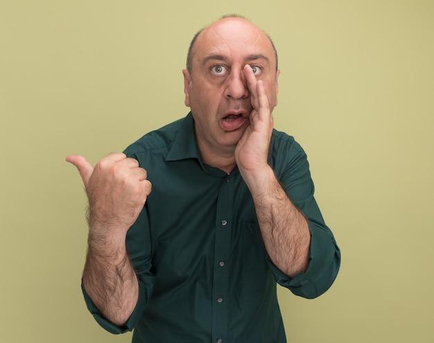 Podejrzany mężczyzna w średnim wieku ubrany w zielony t-shirt szepcze punkty z boku na tle oliwkowej ściany z miejsca na kopię