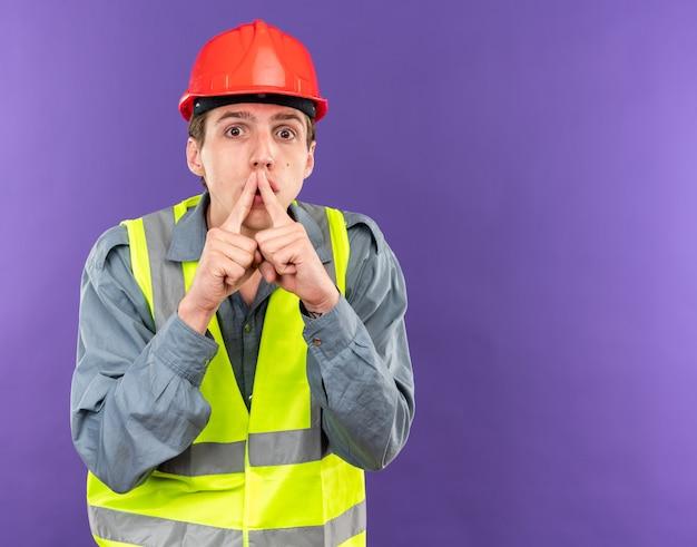 Podejrzany młody budowniczy mężczyzna w mundurze pokazujący gest ciszy odizolowany na niebieskiej ścianie z miejscem na kopię
