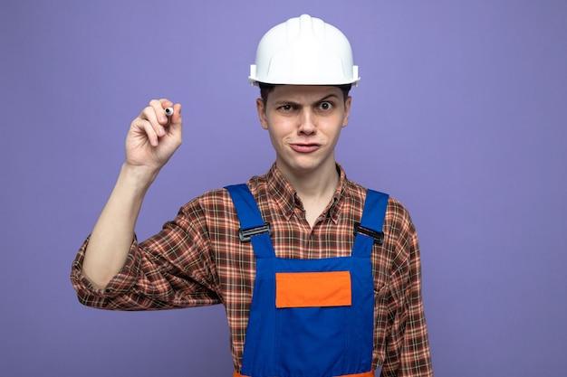 Podejrzany młody budowniczy mężczyzna w mundurze trzymającym marker