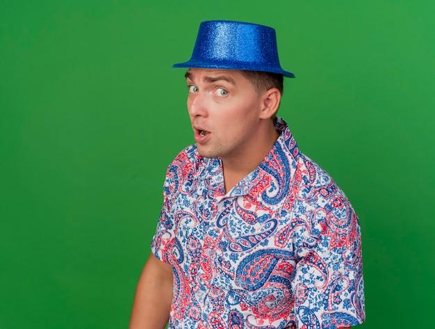 Podejrzany młody partyjny facet patrząc na kamery na sobie niebieski kapelusz na białym tle na zielonym tle