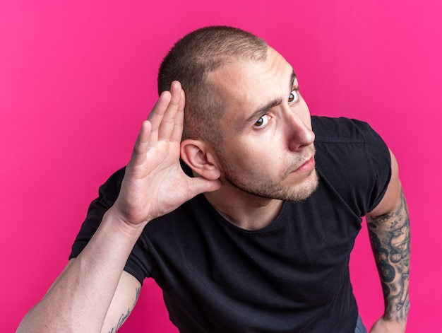 Podejrzany młody przystojny facet ubrany w czarną koszulkę pokazujący gest słuchania na białym tle na różowym tle