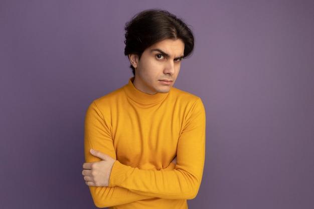Podejrzany młody przystojny facet ubrany w żółty sweter z golfem skrzyżowane ręce na białym tle na fioletowej ścianie