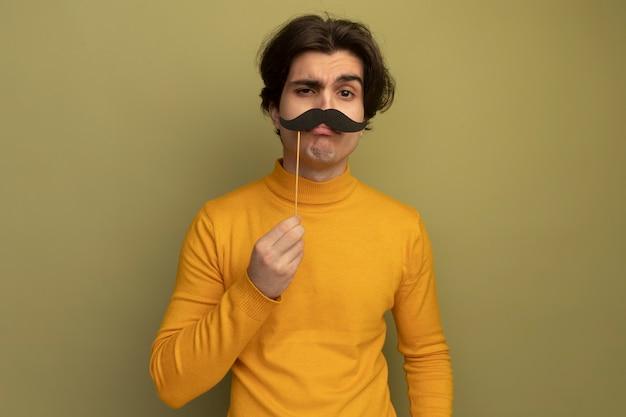 Podejrzany młody przystojny facet ubrany w żółty sweter z golfem, trzymając fałszywe wąsy na kiju na białym tle na oliwkowej ścianie