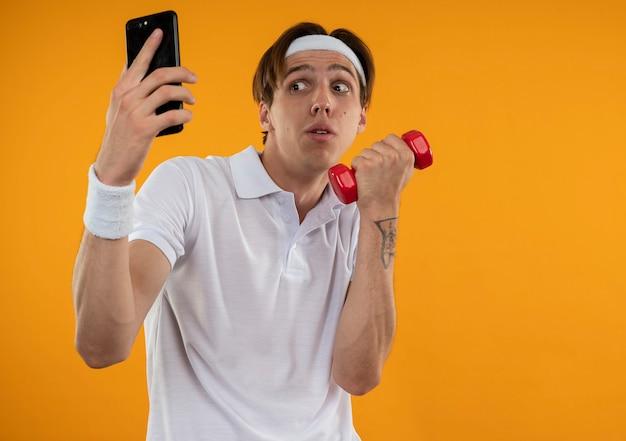 Podejrzany młody sportowy facet ubrany w opaskę i opaskę bierze selfie trzymając hantle odizolowane na pomarańczowej ścianie z miejsca na kopię