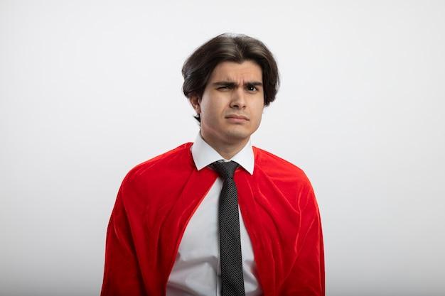 Podejrzany młody superbohater facet patrząc na kamery na sobie krawat na białym tle