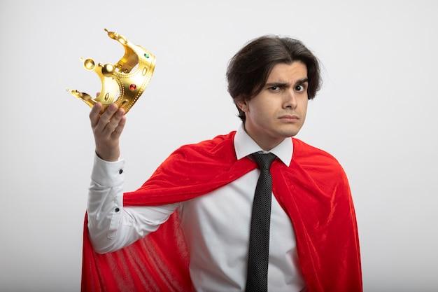 Podejrzany młody superbohater facet sobie krawat trzymając koronę na białym tle