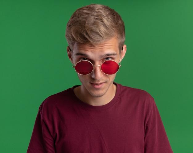 Podejrzany patrząc na przód młody przystojny facet ubrany w czerwoną koszulę i okulary na białym tle na zielonej ścianie