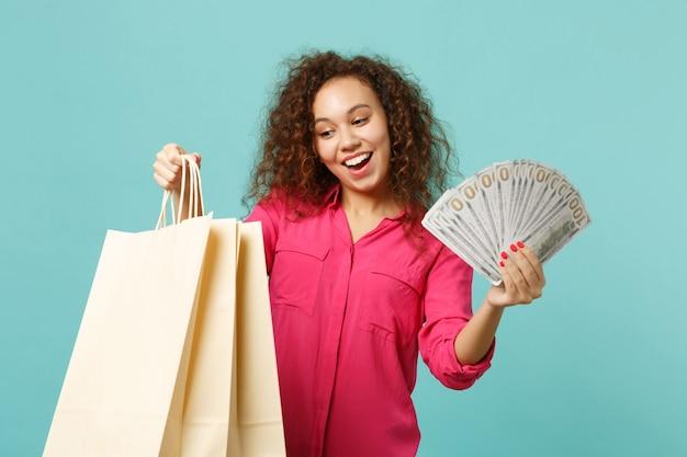 Podekscytowana afrykańska dziewczyna trzymaj torbę z zakupami po zakupach, fan pieniędzy w banknotach dolara, gotówka na białym tle na niebieskim tle turkusu. koncepcja życia ludzi. makieta miejsca na kopię.