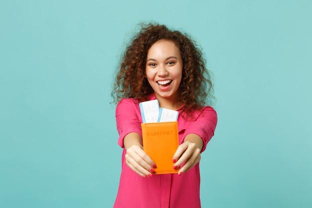 Podekscytowana afrykańska dziewczyna w różowe ubranie trzyma paszport, bilet na kartę pokładową na białym tle na tle niebieskiej ściany turkus w studio. ludzie szczere emocje, koncepcja stylu życia. makieta miejsca na kopię.