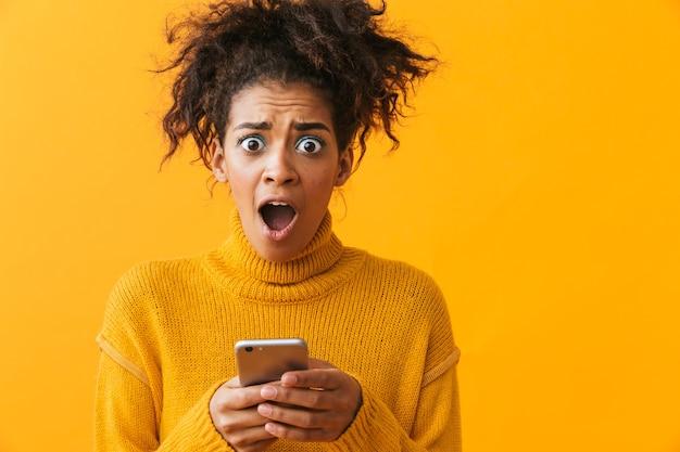 Podekscytowana afrykańska kobieta ubrana w sweter stojący na białym tle, trzymając telefon komórkowy