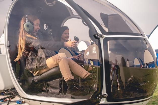 Podekscytowana animatorka w słuchawkach lotnika siedząca w kokpicie helikoptera