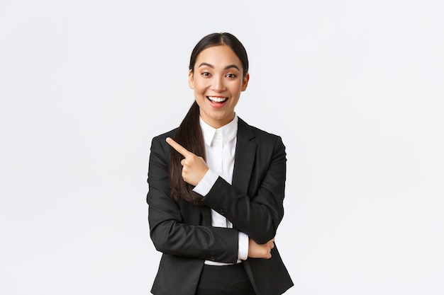 Podekscytowana atrakcyjna azjatycka sprzedawczyni, agentka nieruchomości w garniturze sugerującym idealny dom, stojąca w garniturze i wskazująca palcem w lewo. bizneswoman robi ogłoszenie, pokaż baner