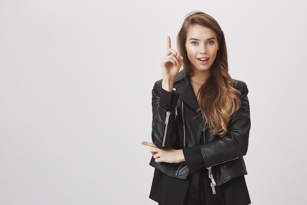 Podekscytowana atrakcyjna kobieta ma pomysł, podnieś palec wskazujący