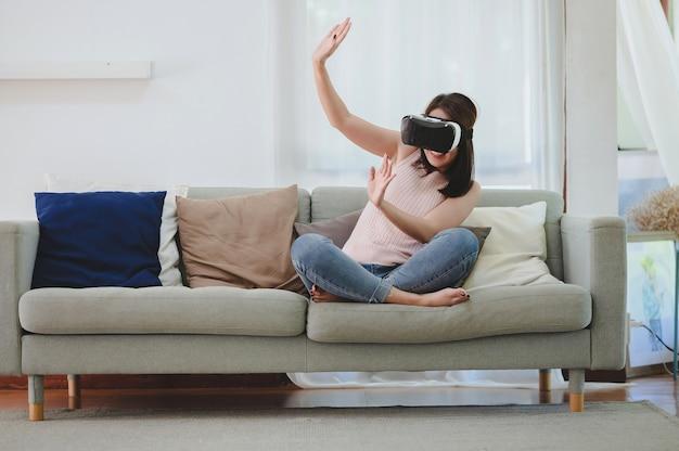Podekscytowana azjatka korzystająca z wirtualnej rzeczywistości zestawu vr w domu w salonie