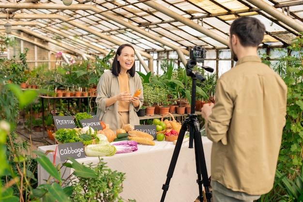 Podekscytowana azjatka trzymająca marchewkę i śmiejąca się podczas kręcenia wideo z kolegą w szklarni