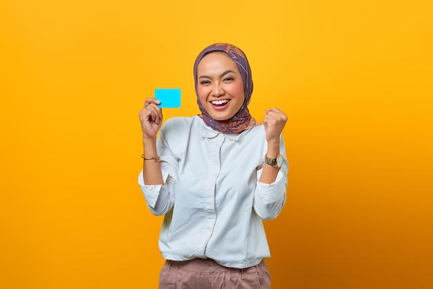 Podekscytowana azjatka trzymająca puste karty z wyrazem zwycięstwa na żółtym tle