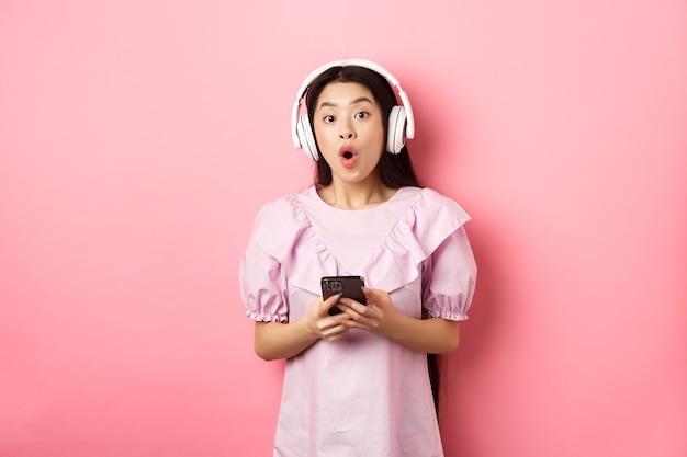 Podekscytowana azjatka w słuchawkach bezprzewodowych mówi wow, trzymając telefon komórkowy i patrząc rozbawiony na aparat, stojąc na różowym tle.