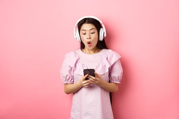 Podekscytowana azjatycka dziewczyna patrząc na ekran smartfona rozbawiona, powiedz wow, słuchając muzyki w słuchawkach bezprzewodowych, stojąc na różowym tle.