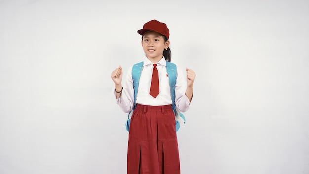 Podekscytowana azjatycka dziewczyna w szkole podstawowej na białym tle